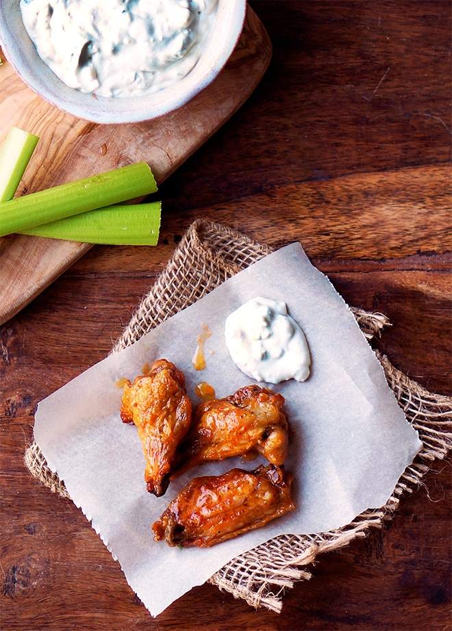 crispy oven baked chicken wings with celery sticks and homemade blue cheese