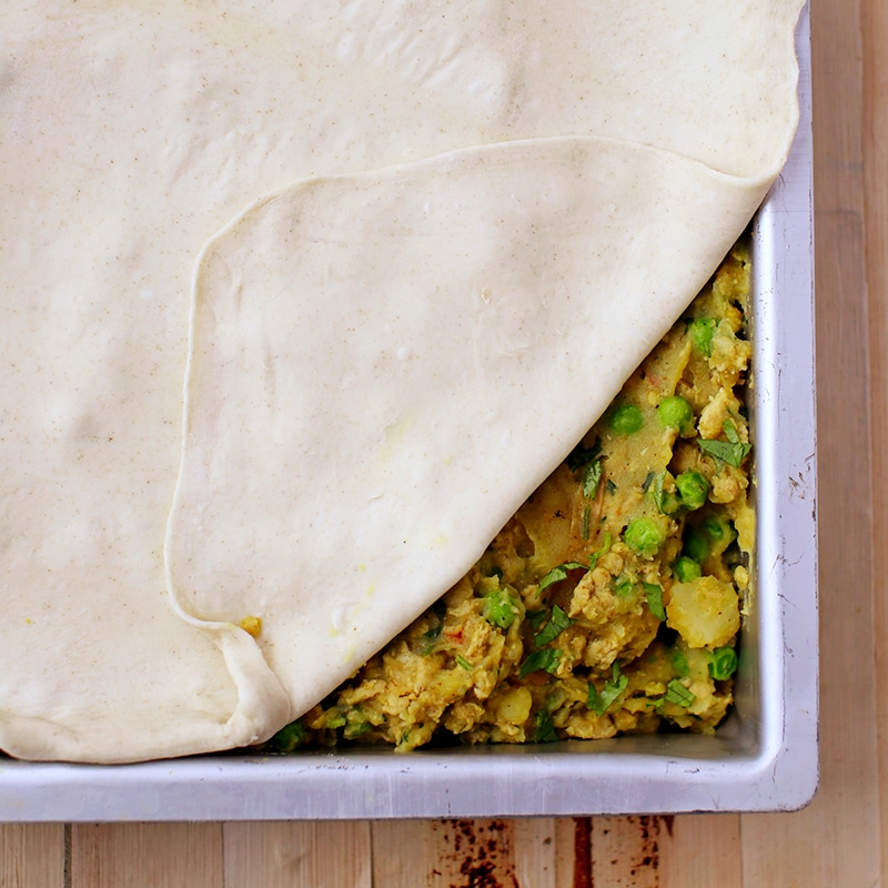 samosa filling in a casserole dish with raw pie dough on top