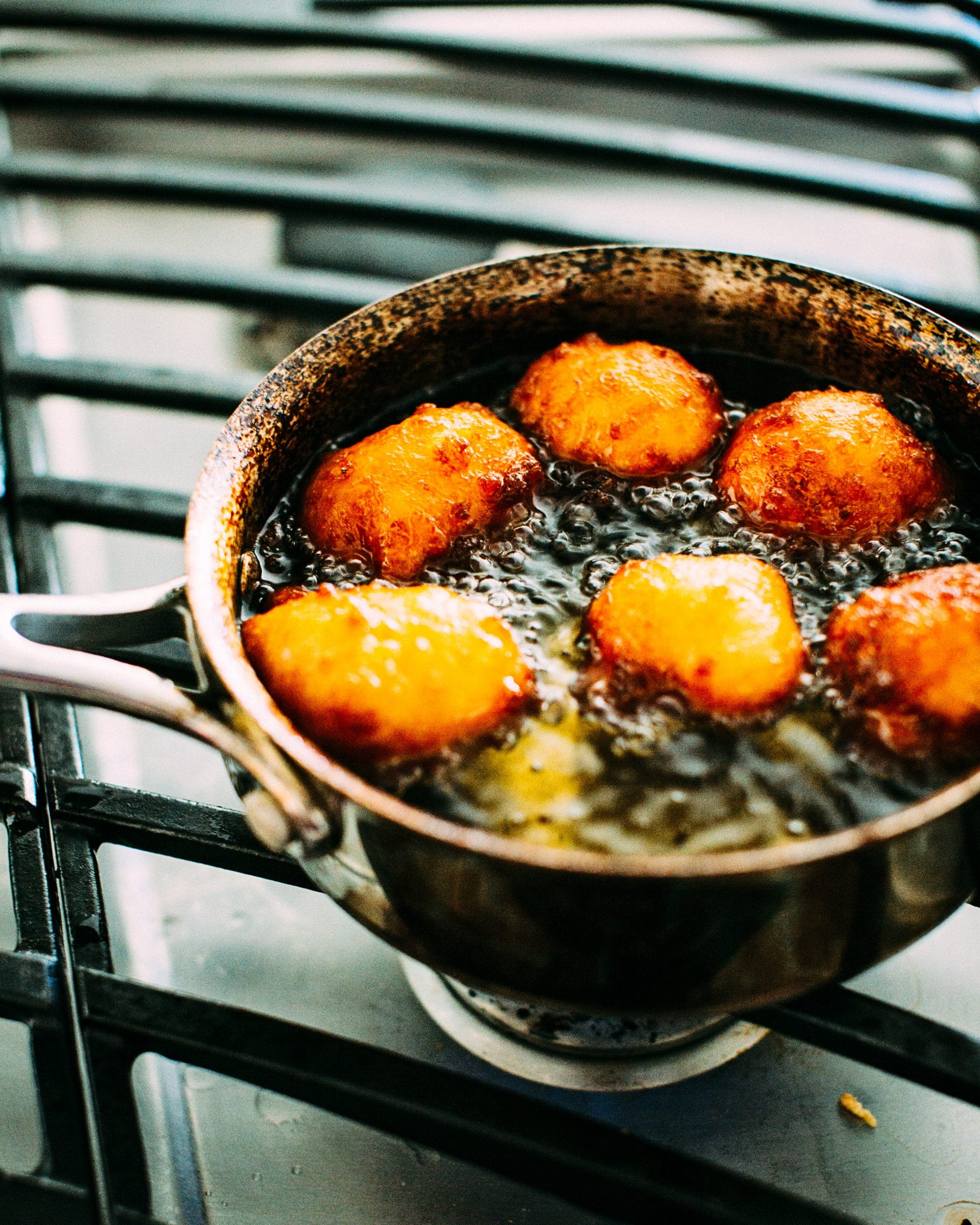 gulab jamun being fried on a stovetop