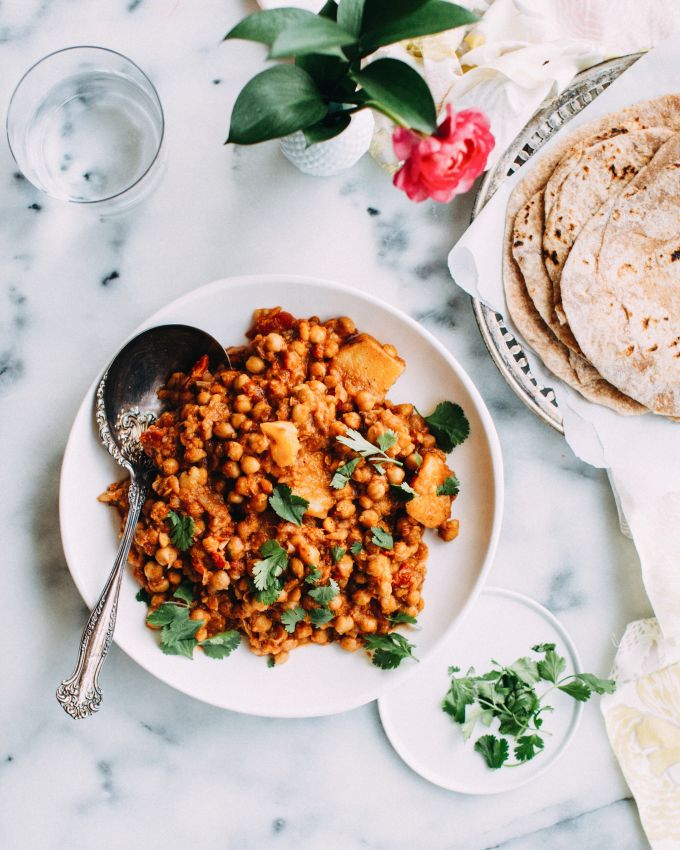 vegan indian chickpea curry with whole wheat tortillas and a glass of water