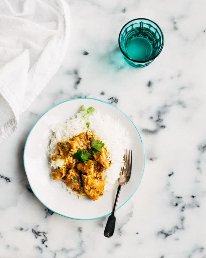 easy pork vindaloo curry on a marble counter with a blue glass