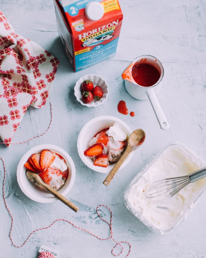bowls of banana ice cream with strawberries and a jug of milk