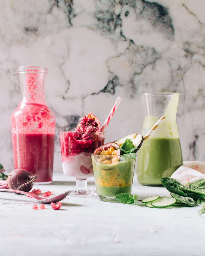 jar and glass of green smoothie beside a pink smoothie on a table