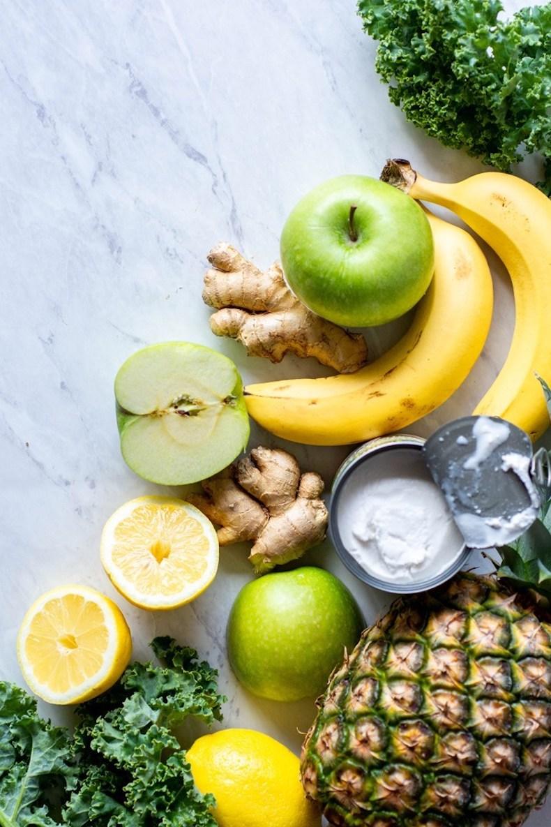 green apple, ginger, lemon, banana and pineapple on marble backdrop