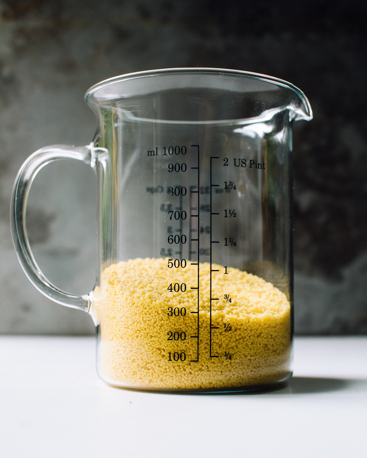 dry couscous in a measuring cup
