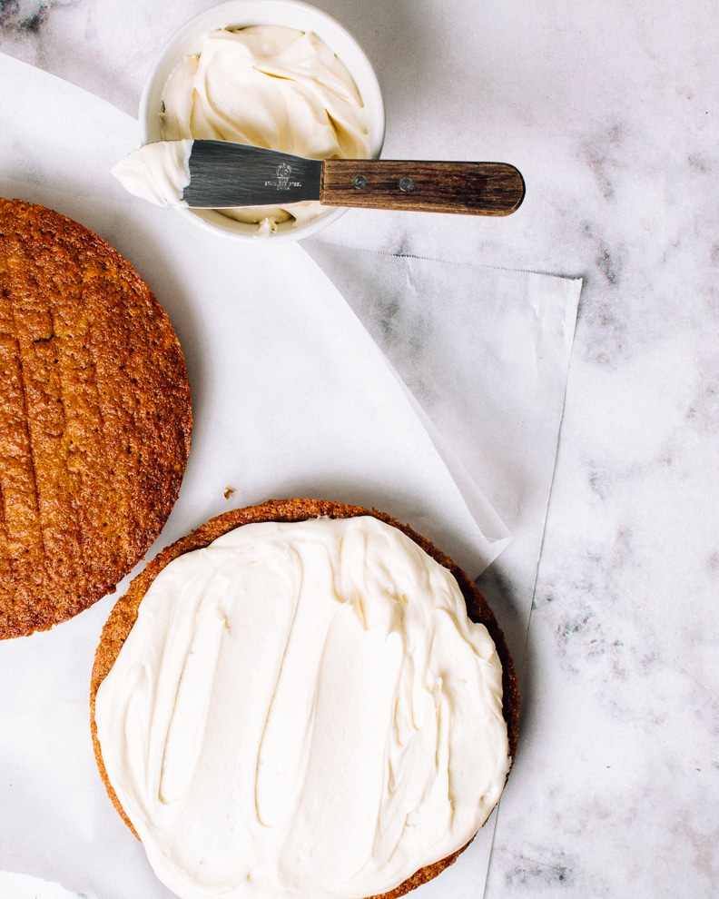 two tiers of a homemade carrot cake with cream cheese icing in a dish