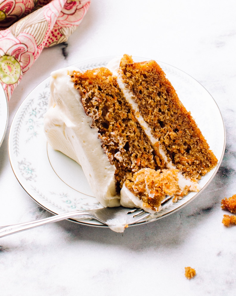 slice of moist carrot cake with two tiers and cream cheese frosting