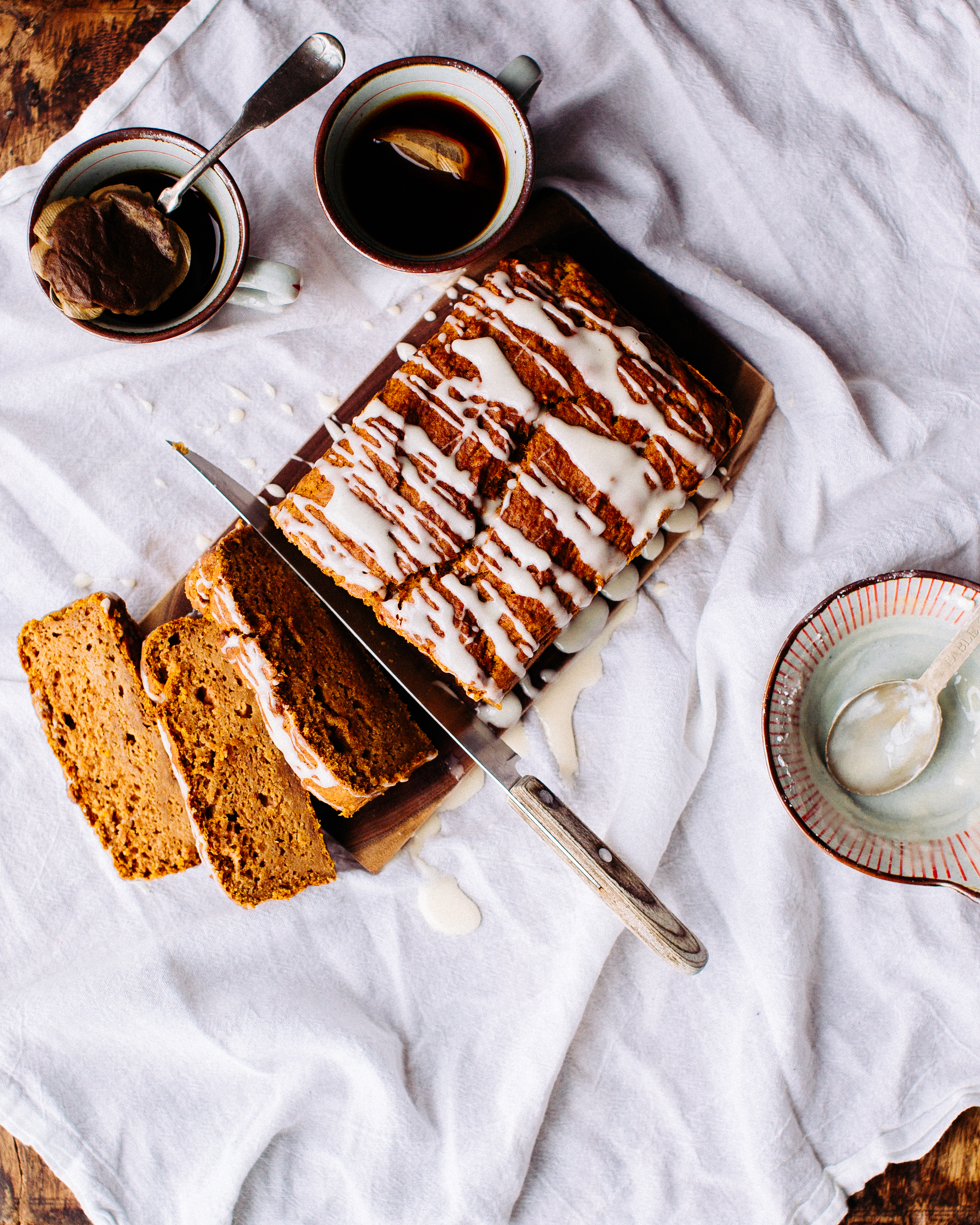 homemade pumpkin bread with cream cheese frosting drizzled across it and a cup of black tea